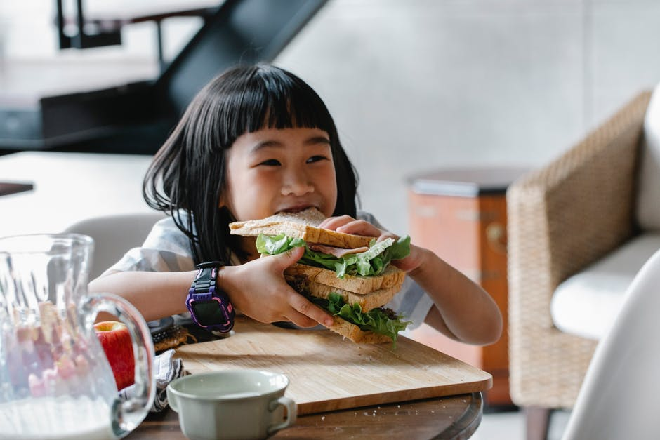 A little girl sitting at a table eating food